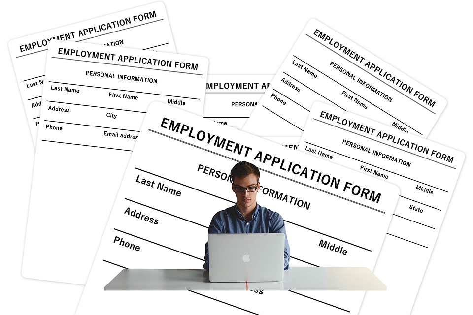HR forms surrounding man on computer